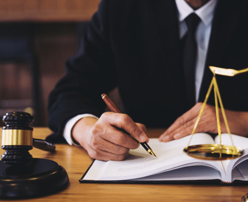Advocate in office writing application with scale and gavel on table
